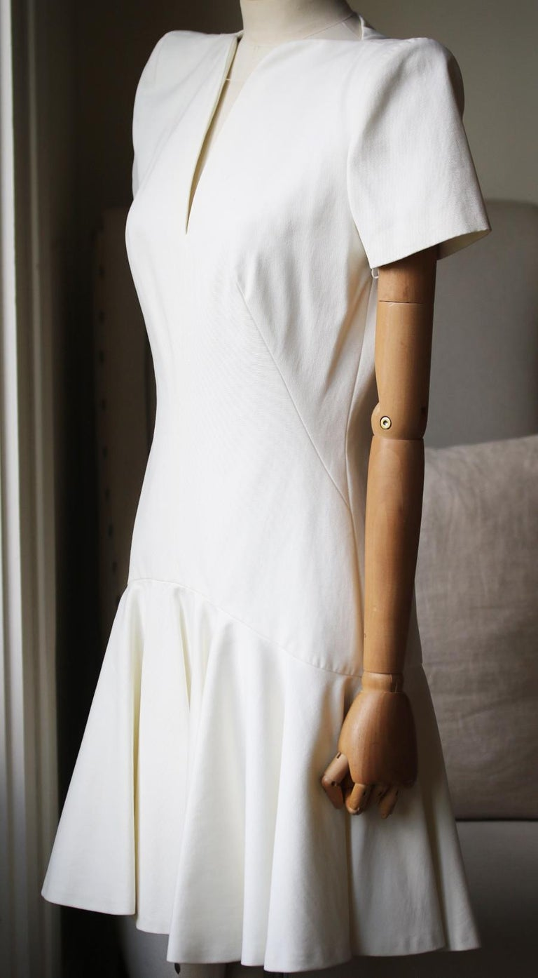 Ivory crepe. Shoulder pads, fluted insert at skirt, fully lined. Concealed hook and zip fastening along back. 50% Acetate, 50% rayon. Lining: 74% acetate, 26% silk.   Size: IT 42 (UK 10, US 6, FR 38)  Condition: New with tags.