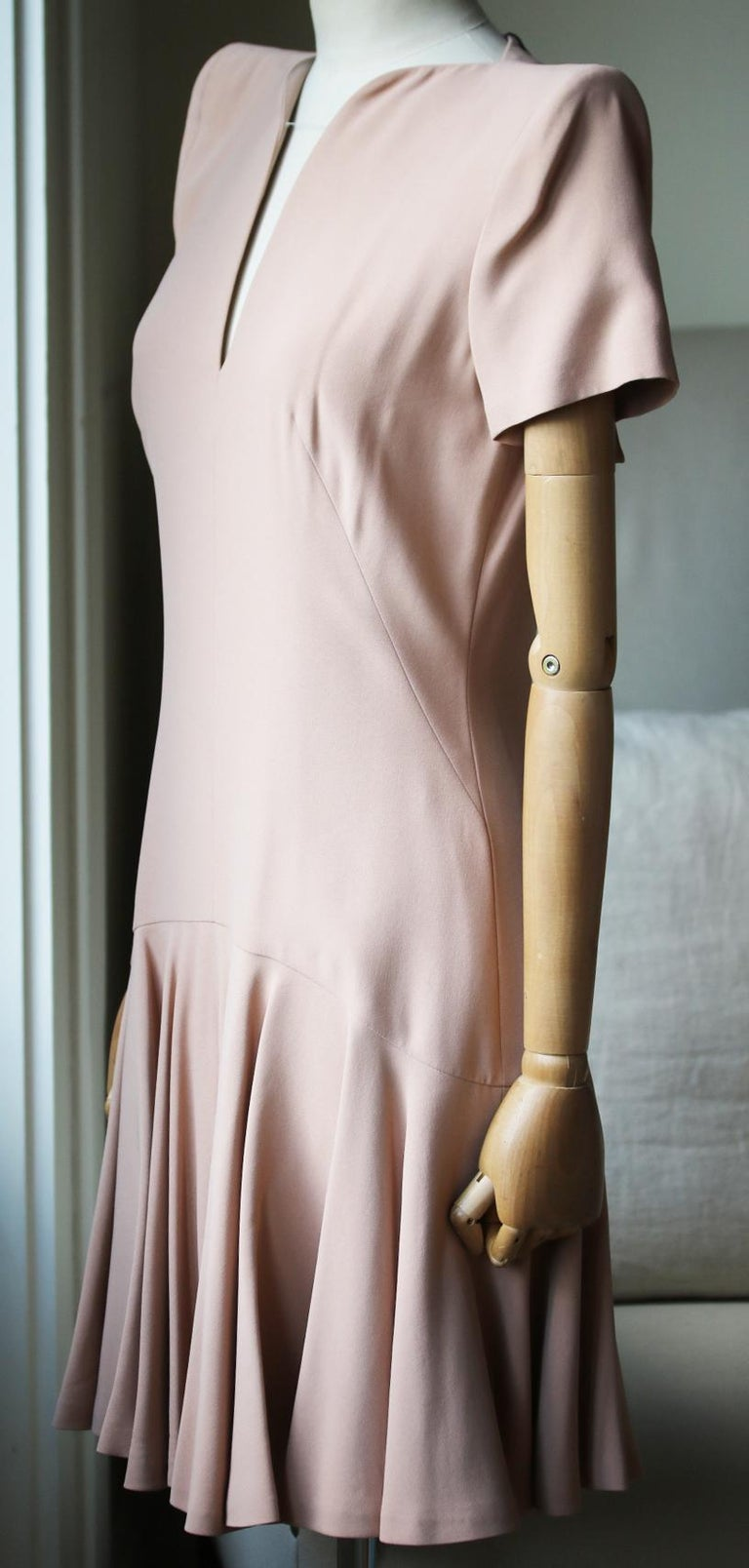 Blush-pink crepe. Shoulder pads, fluted insert at skirt, fully lined. Concealed hook and zip fastening along back. 50% Acetate, 50% rayon. Lining: 74% acetate, 26% silk.   Size: IT 42 (UK 10, US 6, FR 38)  Condition: New with tags.