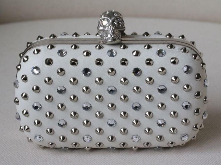 Alexander McQueen napa leather clutch with silvertone studs and crystals. Signature hinged crystal-embellished skull clasp. Framed hard-shell design with rounded corners. Made in Italy.  Dimensions: Approx. 14 x 9 x 5 cm   Condition: As new