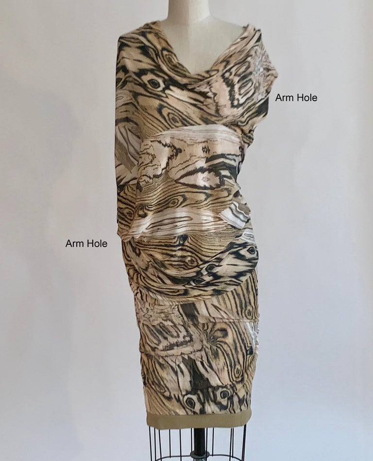 Alexander McQueen brown knit wood grain print dress with asymmetrical drape detail. One arm ends near shoulder and other drapes in a bit of a batwing style with opening near lower arm. Stretchy rib knit at hem that can be worn long, or pushed up and
