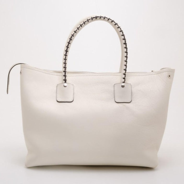 This Alexander McQueen White Folkstitch tote is just what every city girl needs. Crafted from crisp white leather, it is beautifully detailed with brown stitching, a front zip pocket, tassels, leather ID tag and rolled leather handles. The interior