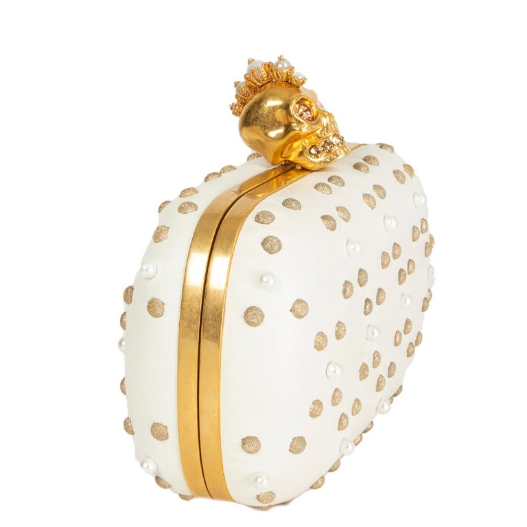 Alexander McQueen skull box clutch in off-white lambskin embellshed with pearls and light gold-tone studs featuring gold-tone metal skull closure with crystal eyes and teeth. Lined in off-white calfskin. Has been carried with one missing pearl on