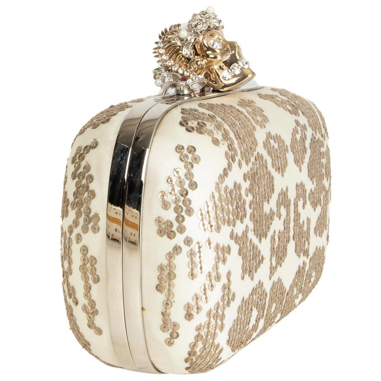 Alexander McQueen skull box clutch in off-white satin embellshed with antique silver-tone sequins and light gold-tone skull closure with crystal eyes and teeth. Lined in off-white calfskin. Has been carried with some oft discoloration on the buttom.