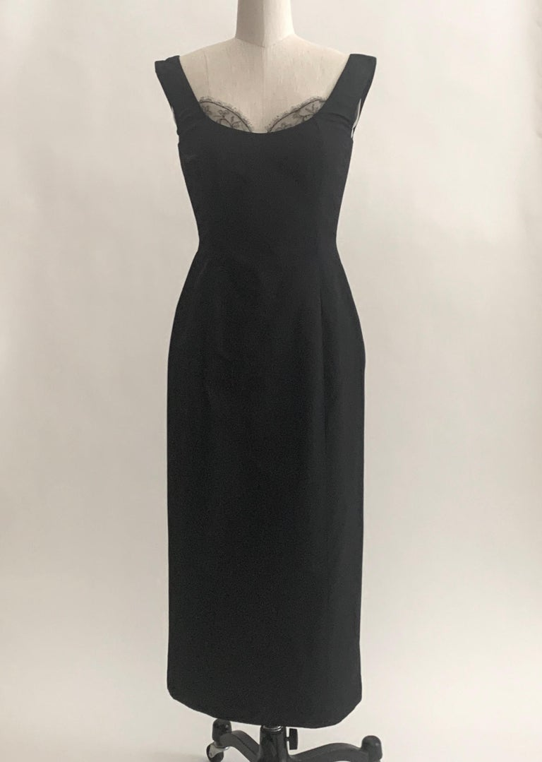 Alexander McQueen black silk dress from the 2005 Hitchcock inspired collection 'The Man Who Knew Too Much,' which channeled Tippi Hedren and Marilyn Monroe. Fitted midi length silhouette with lace accent at bust. Boned at upper bodice. Back zip and