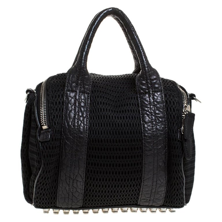 Creations like this Rocco bag by Alexander Wang never go out of style. This black bag is crafted from crochet fabric and leather and it features dual handles and silver-tone hardware. The top zipper opens to a nylon interior sized to carry your