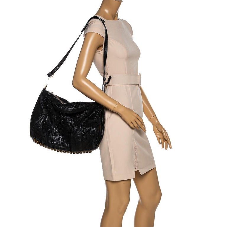 Creations like this Rocco bag by Alexander Wang never go out of style. This black bag is crafted from leather and it features dual handles, and a shoulder strap, and gold-tone hardware. The top zipper opens to a fabric interior sized to carry your