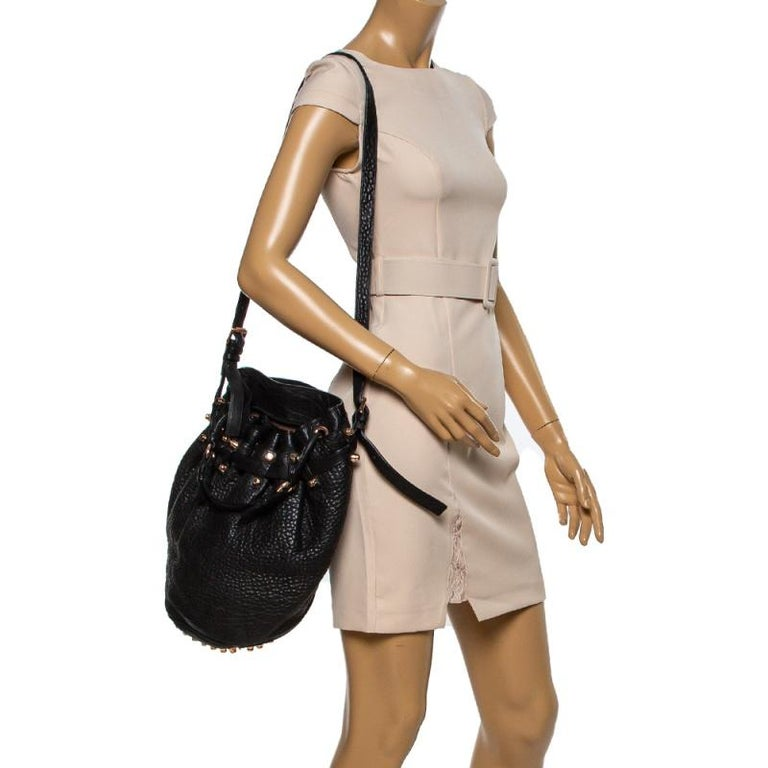 This chic Diego bucket bag from Alexander Wang offers ample style and reliability. Crafted from black leather, the bag features a single top handle, an adjustable shoulder strap, and protective metal feet at the bottom. The drawstring closure opens