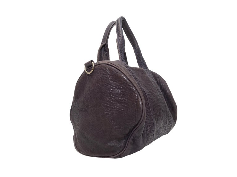 Product details: Brown leather Rocco duffel bag by Alexander Wang. Dual handles. Optional shoulder strap. Zip closure at top. 13