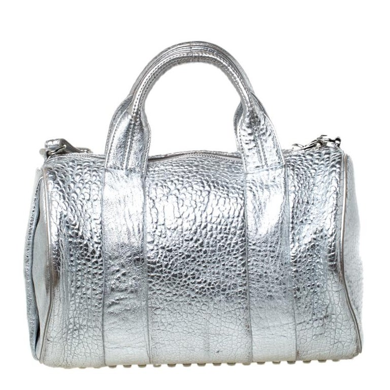 Creations like this Rocco Duffle Bag by Alexander Wang never go out of style. This silver bag is crafted from pebbled leather and it features dual handles, a detachable shoulder strap, and studs on the bottom. The top zipper opens to a fabric
