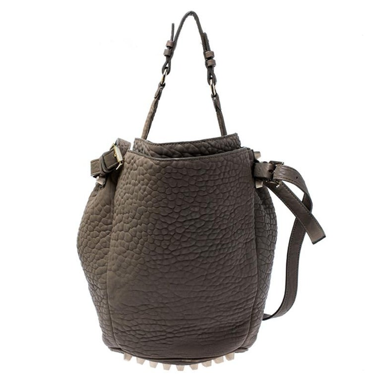 This chic Diego bucket bag from Alexander Wang is not only a symbol of style but also reliability. Crafted from taupe textured leather, the bag features a single top handle, an adjustable shoulder strap and protective metal feet at the bottom. The