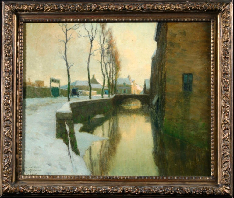 A wonderful oil on original canvas by French impressionist painter Alexandre Louis Jacob depicting a river running in between houses and a road, with bare trees beside it and a bridge over it. The scene is set in winter and snow coats the road and