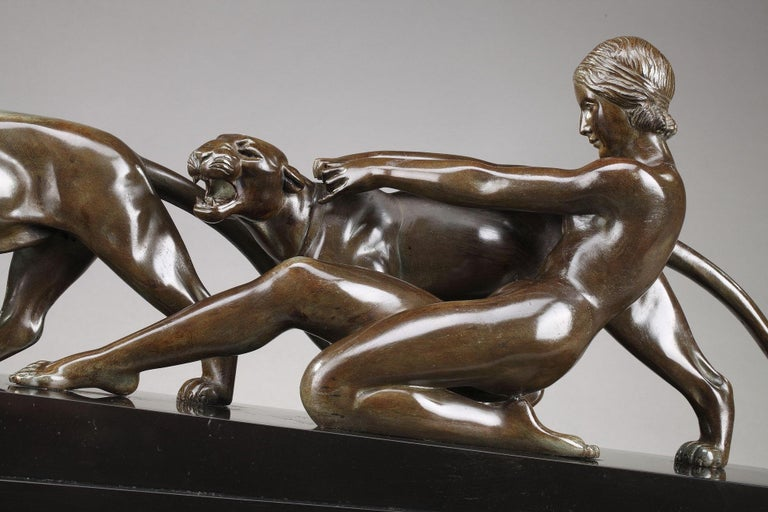 Art Deco group crafted in bronze with brown patina featuring a woman holding a panther. The two animals and the woman rest on a black marble pedestal. Signed on the terrace: Ouline (for Alexandre Ouline). Alexandre Ouline was an Art Deco sculptor,