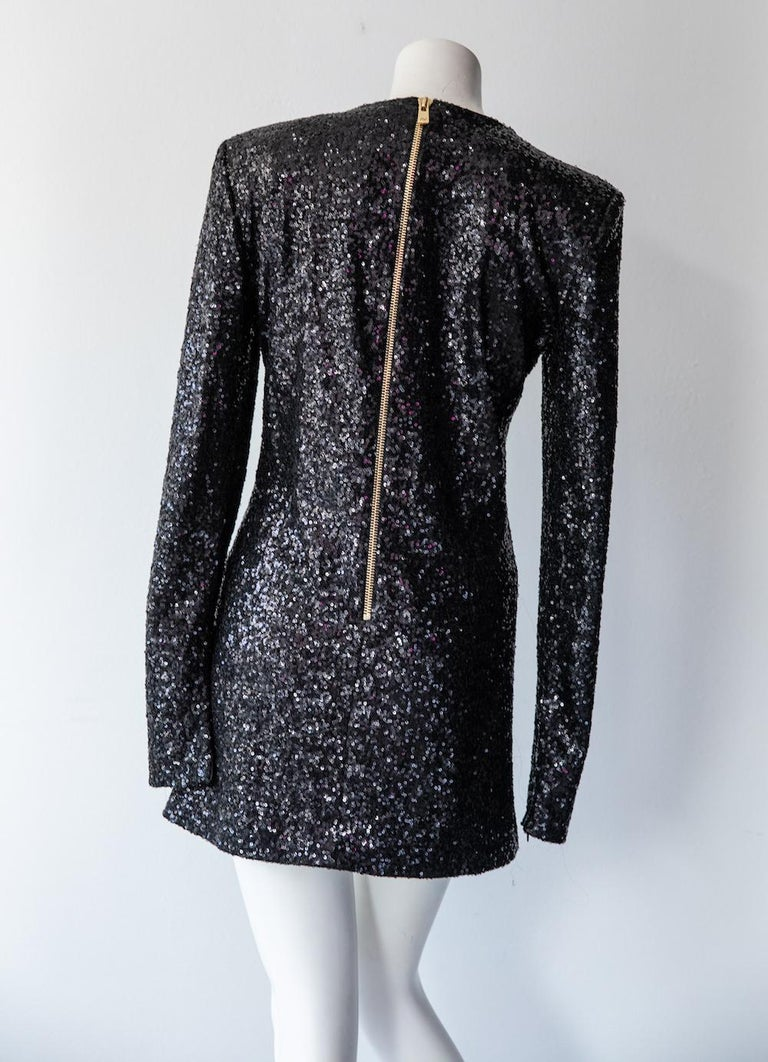 Long sleeve cocktail dress by designer Alexandre Vauthier for his namesake label. Vauthier designed this structured mini dress before beginning his tenure at Saint Laurent. It features a black mini-sequins all over, with a heavy gold exposed zipper