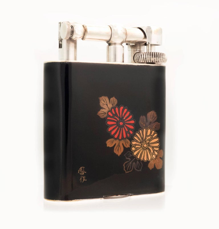 An extremely scarce 'Namiki' table lighter in 'Giant' table size with silver-plated hardware with a glossy black background with a red and yellow chrysanthemum with foliage to the front, and three gold and red flowers with foliage to the reverse.