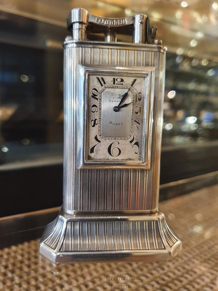 Alfred Dunhill, London  A very scarce Sterling silver table lighter with clock, the body with fine linear pattern is complete with Dunhill's trademark signed, 'lift-arm'. The Club Clock, as it is known, was their first table lighter to incorporate