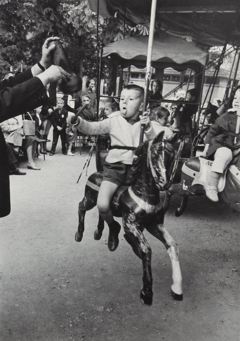 Alfred Eisenstaedt Black and White Photograph - Boy with Tongue Out Spearing Brass Ring, Luxembourg Garden, Paris