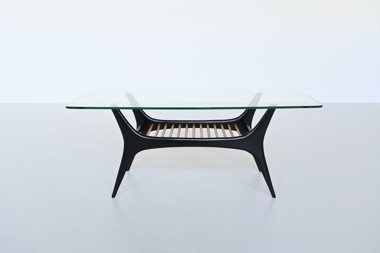 Beautiful sculptural coffee table designed by Alfred Hendrickx and manufactured by Belform, Belgium 1958. This coffee table has an black lacquered organic shaped base with slender wooden rots that supports a rounded edged glass top. This model is a