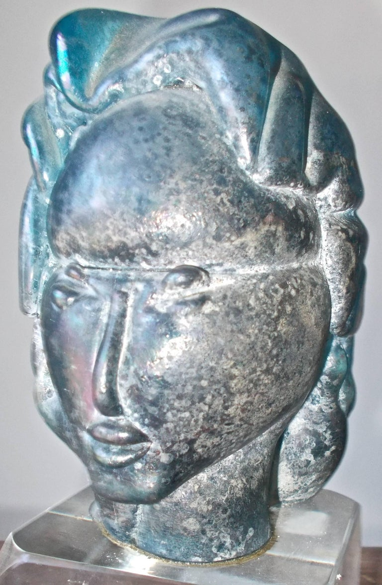 A unique piece sculpted of Iridized blue glass (measurements are of the head itself) sits on a clear 3 1/8