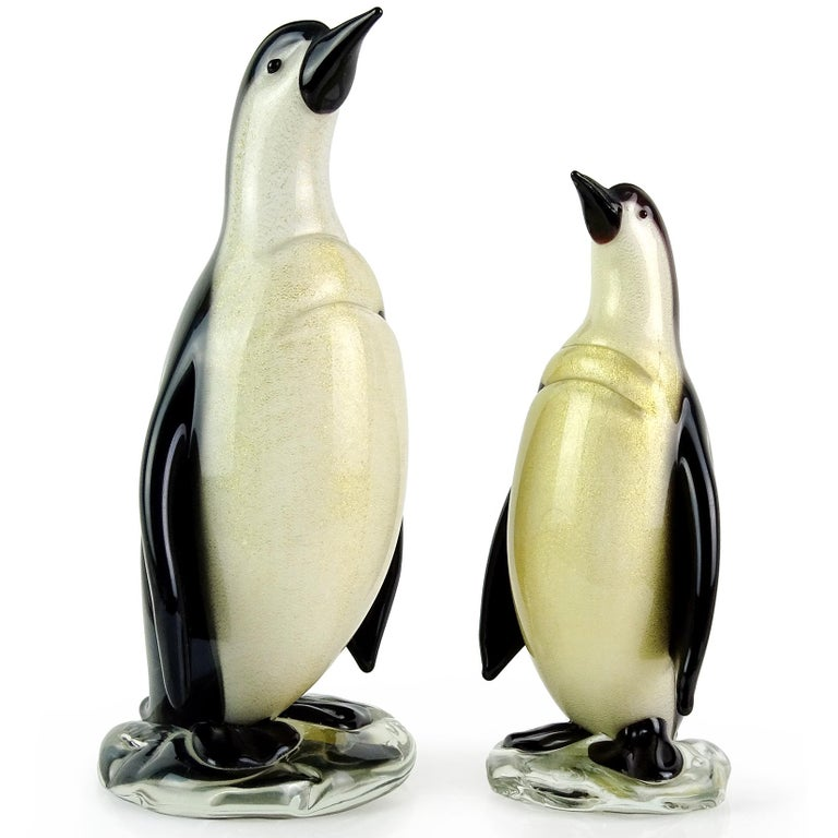 Beautiful Murano hand blown black, white and gold flecks Italian art glass penguin sculptures. Documented to designer Alfredo Barbini, with original gallery item labels. Published in his catalog as well. They are both covered in gold leaf, and stand