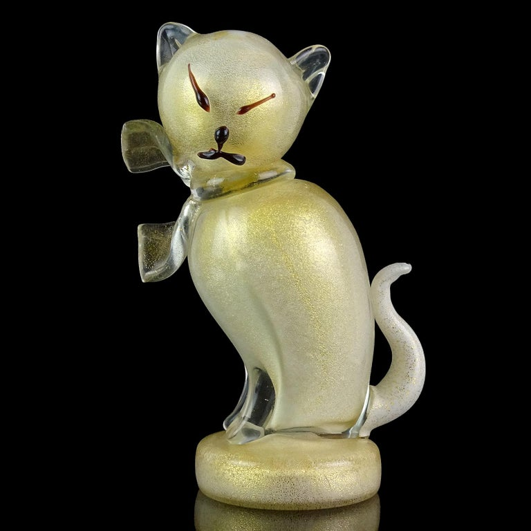 Beautiful vintage Murano hand blown white and gold flecks Italian art glass kitty cat sculpture figurine. Documented to designer Alfredo Barbini. The piece is profusely covered in gold leaf, with clear bow around its neck. Stands on a round disk,
