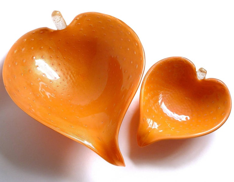 Beautiful set of vintage Murano hand blown orange, gold flecks and controlled bubbles Italian art glass leaf shape bowls. Attributed to designer Alfredo Barbini, circa 1950s-1960s. Both pieces are profusely covered in gold leaf, and have attached