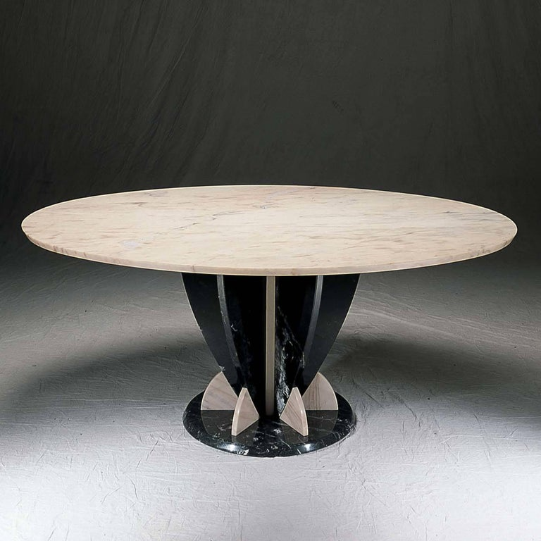 Sole protagonist of a sophisticated dining room, this table is an aesthetically stunning piece that combines the preciously elaborated base made of black Marquinia marble with a sleek, round top of pink Portogallo marble. The monolithic structure is