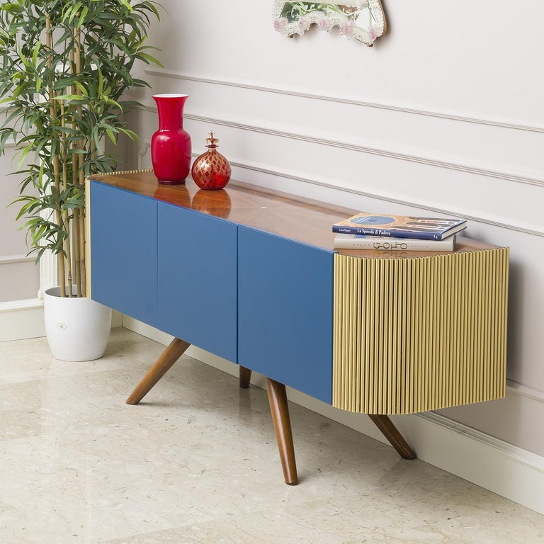 A modern and innovative designed sideboard that has a wooden body and a radial walnut top with mother of pearl carved into the center. The legs are made of walnut, while the wooden doors are lacquered blue. In contrast the sides are in brushed