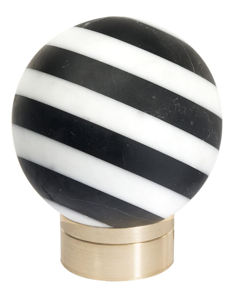 Inspired by the captivating black and white stone buildings found across Europe, this exceptional table lamp will cast an alluring glow in a traditional or Minimalist decor. Mounted on a circular brass base with a gold finish, the orb-shaped lamp is