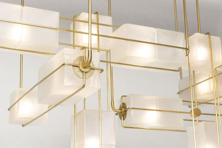 The Alice collection is inspired by Brutalist modular architecture. The textured hand blown glass cubes are sandblasted to create a soft glow and stacked together to diffuse light in different intensities. The frame is made of solid brass or