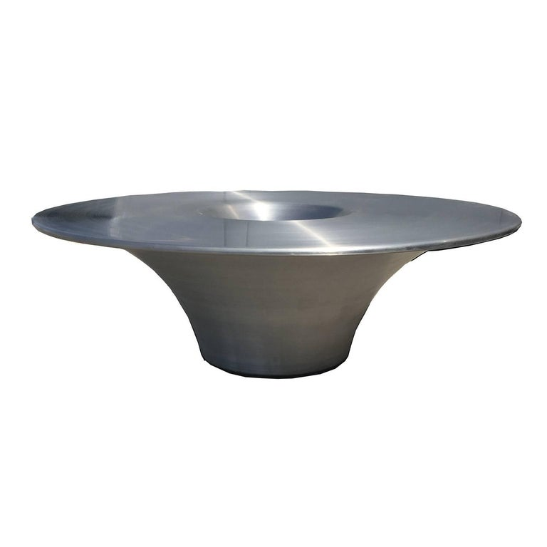 Created in the 1990s, this marvellous table references alien space craft with its' futuristic design. Of special note is the inset centre, as a catch all functional centre or chips bowl. The table is in fine original condition with raised label near