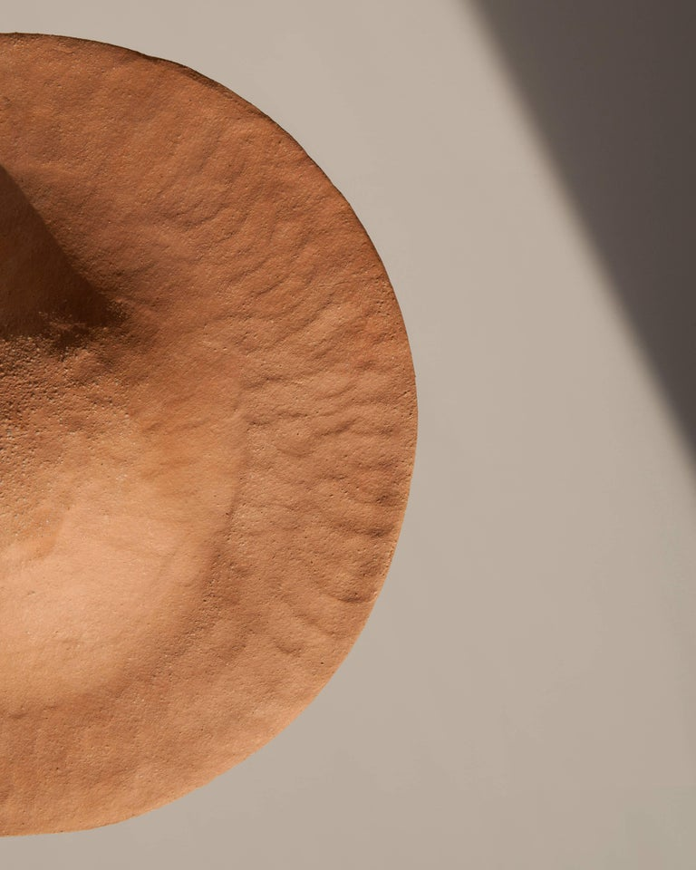 Each of the stoneware shades is handmade in the Foothills of the Appalachian Mountains in South Eastern Ohio. The grogged and toothed clay bodies are hand-pressed onto molds making each one-of-a-kind. The Alien shade is adjustable providing