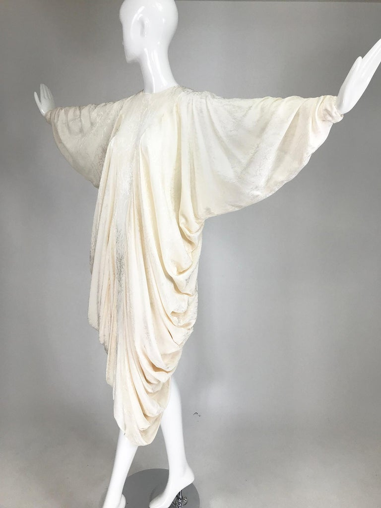 Alik SInger cream silk jacquard bias draped bat wing dress from the 1980s. 100% silk dress in cream with a modernist design. Bias cut dress has a jewel neckline with long bat wing sleeves, the sleeves are shirred at the top about the elbow bend, to