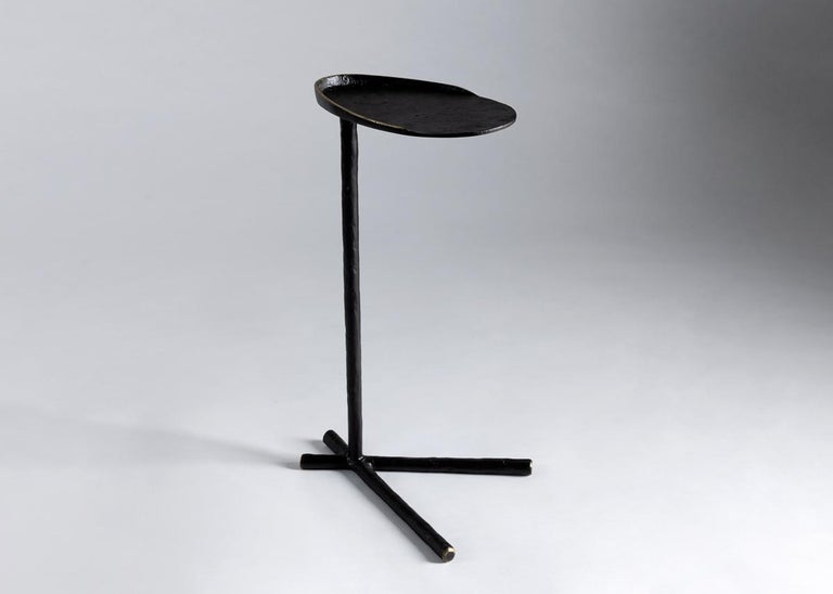 The long, bird-like feet of this discrete, organic side table lend it a slightly whimsical feel. On a more practical level, its c-shaped design means that when it is not in use, the table can be slid into place beside a sofa or a chair and tucked