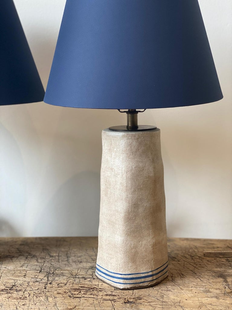 Handmade lamp bases by the French American artist Alix Soubiran. The lamps come with brown twist cord. Sold as a pair, navy custom bookcloth shade included.  The lamp base measures 11
