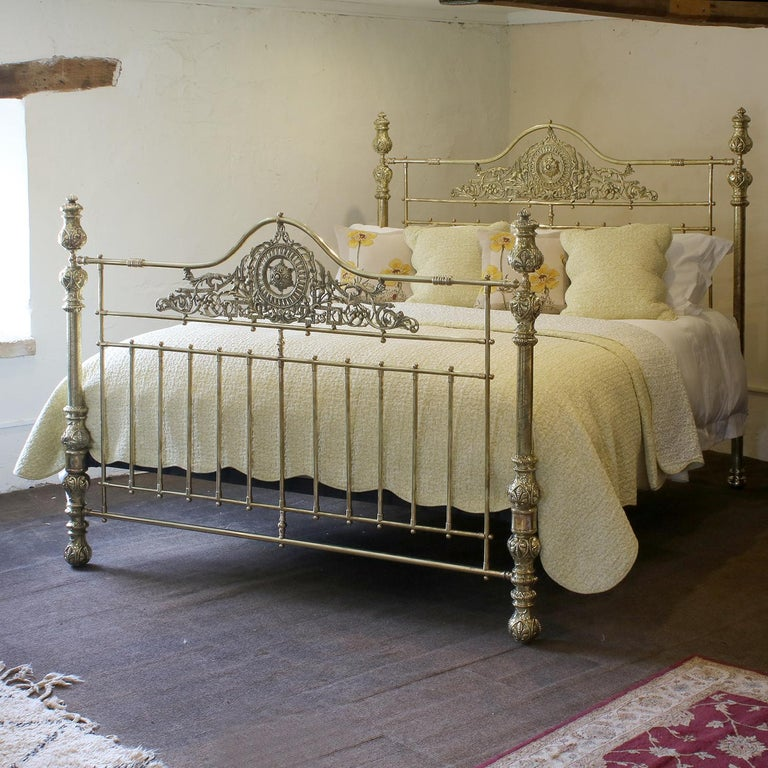 A superb all brass 6ft wide antique bed with serpentine brass top rails, decorative central brass castings, rare etched posts and ornate brass fittings.