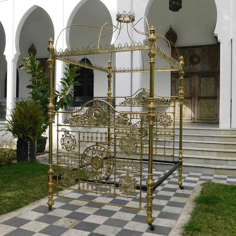 A majestic all brass four poster bed bedstead with crown and canopy. Detailed etched brass posts, displaying ornate brass fittings, support an impressive canopy, with decorative fretwork castings, surmounted by a brass crown. The two superbly