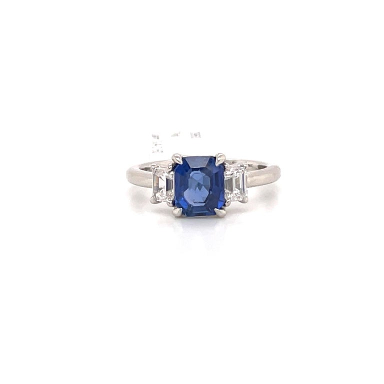 All GIA Certified three stone ring featuring one center Radiant cut Sapphire weighing 1.85 carats flanked with two Emerald cut diamonds weighing 0.60 carats. Diamonds are GIA Certified D-F VS1