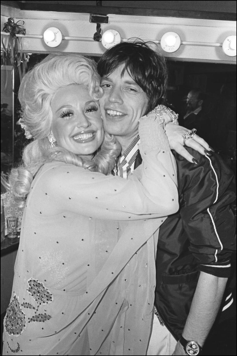 """Country music star Dolly Parton hugs rock star Mick Jagger backstage after her Bottom Line concert in NYC, 5/14/77. Signed and numbered by the Photographer Image size 20"""" X 30"""" on 24"""" X 36"""" paper. Edition of 15."""