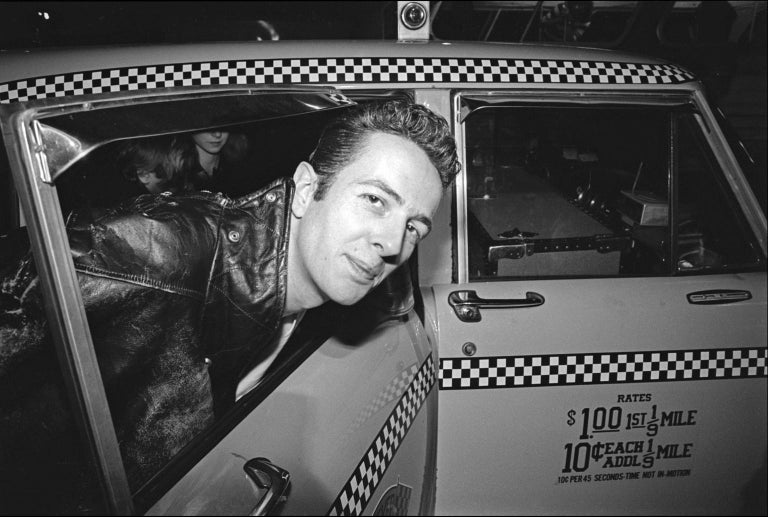 "Joe Strummer, guitarist for The Clash, gets into a taxi at JFK Airport as the band arrives for a U.S. tour in 1981. Numbered and signed by the photographer. Image size 36"" X 54"" on 44"" X 66"" paper. Edition of 10."