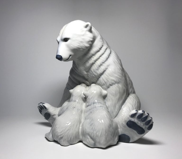 Created by Allan Therkelsen for Royal Copenhagen, this white porcelain polar bear and her two cubs were from the 'Motherly Love' series of figures. Beautifully sculptured and hand painted using the underglaze technique, a method of painting the