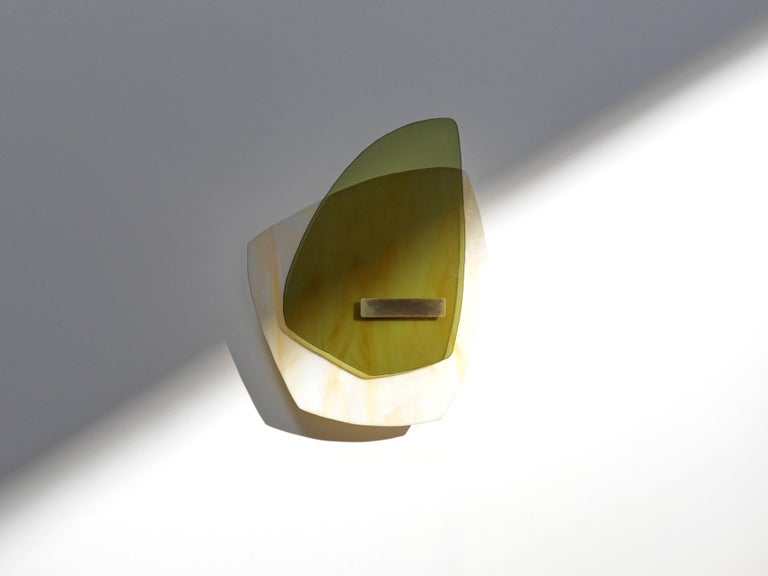 Alliance 03 light sculpture by Marie Jeunet  Dimensions: H 35 x L 26 cm Materials: Semi opaque ochre marbled glass, smooth olive green glass sheet, brushed brass structure and finish  Les Precieux These luminous sculptures evolve with the