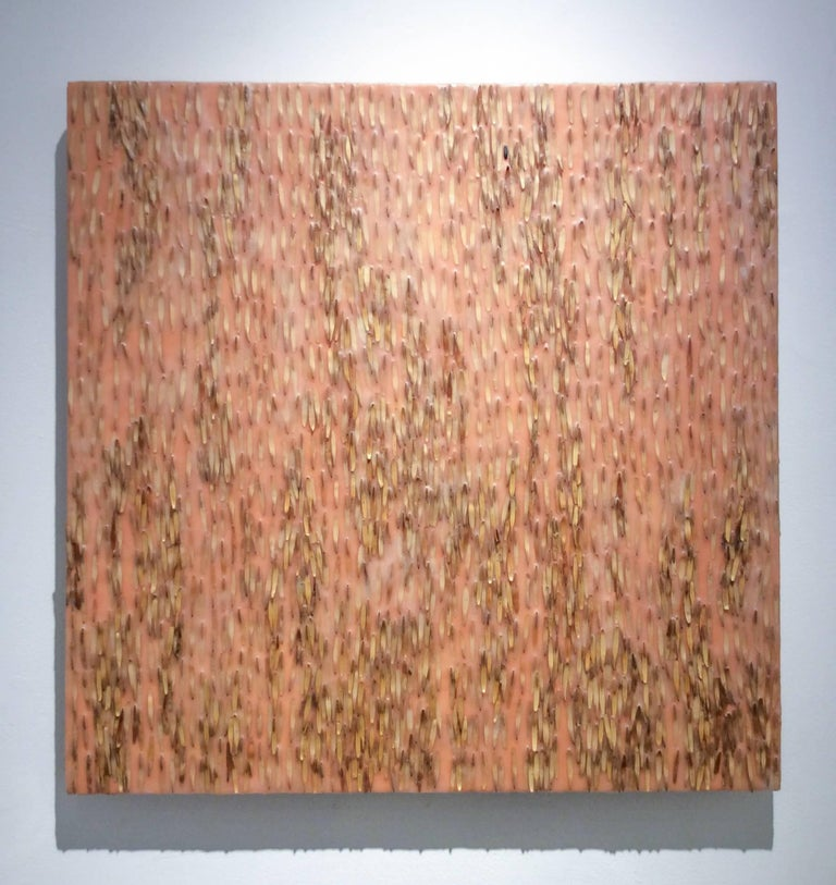 Abstract encaustic painting with dark brown and beige ash keys against a light orange, peach background 24 x 24 x 1.5 inches   This modern abstract encaustic painting by Allyson Levy is made with assorted beige and light brown ash keys encased in a