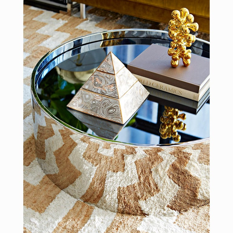 Futuristic reflection. Minimalist and modern, our Alphaville cocktail table shines in polished stainless steel with a smoke mirror top. The simple drum form is a solid anchor for any room, while the reflective surface keeps the feeling light and