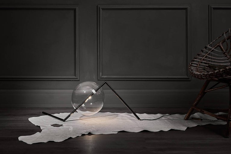 "Designed to be positioned on the floor or on a console, the Alpi Floor/Table Lamp is a work of Abstract Art for the home. The exact arrangement of this Sculptural Decorative Piece can be adjusted using the nickel ring, and with the ""inline Touch"