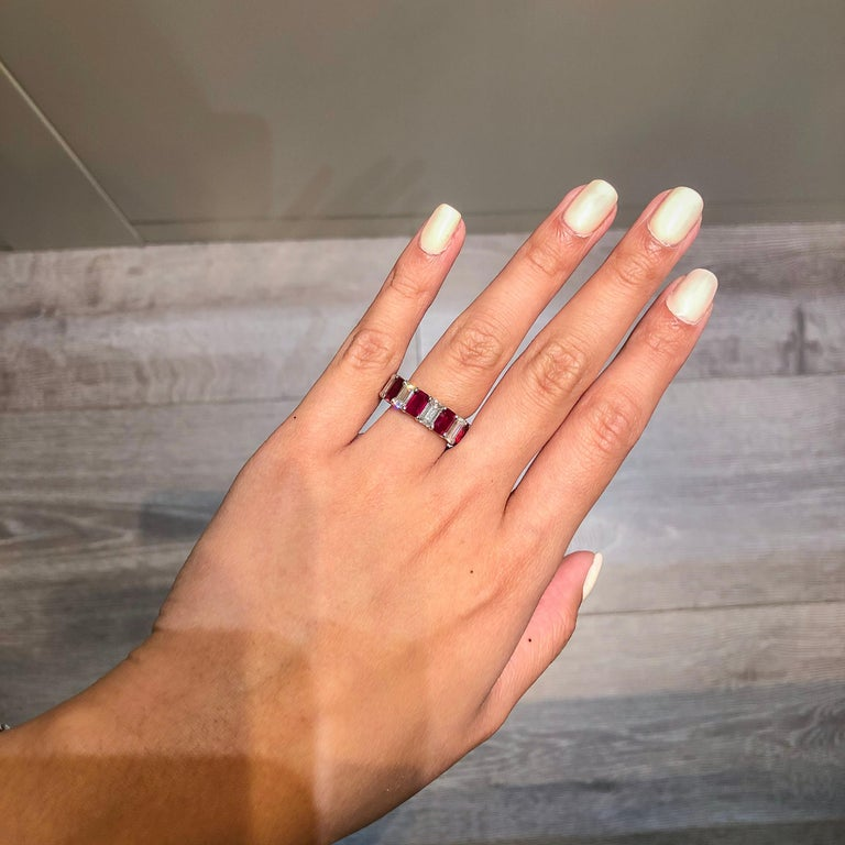This gorgeous eternity band features 9 natural emerald cut rubies weighing 5.89 carats total that alternate with 9 emerald cut diamonds weighing 4.82 carats total. Set in an eternity style setting. Made with platinum. Approximate size is 6 (limited