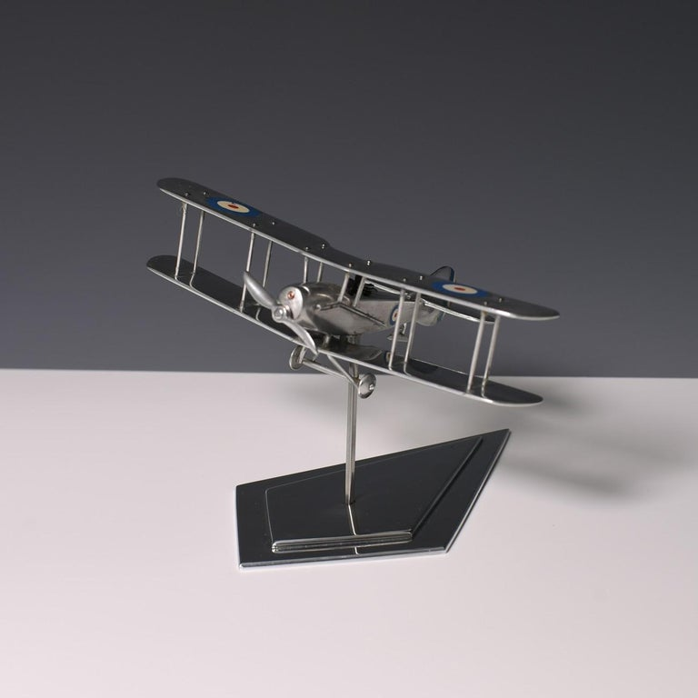 A delightful polished aluminium bi-plane model on stand, made in the 1980s. With resin figures of the gunner and pilot.  Dimensions: 16.5 cm/6½ inches (wingspan) x 11.5 cm/4½ inches (length) x 12 cm/4¾ inches (max height)  Bentleys are Members of