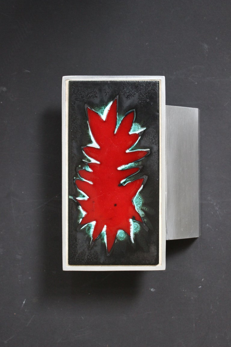 A single aluminium door handle with ceramic panel of abstract design, Belgium, 1960s.  The ceramic has a central zone of deep glossy red (see main image for best depth of color), surrounded by flashes of green and white; on a background of deep