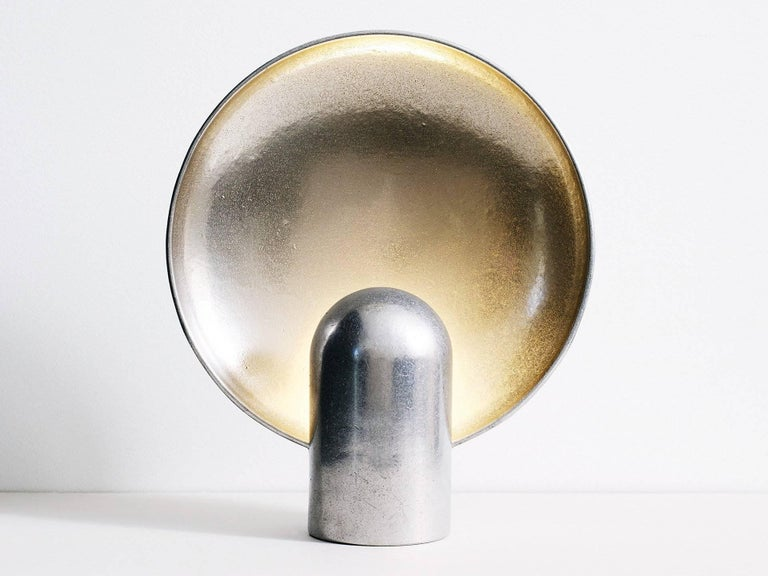 The surface sconce is a ambient, sculptural light cast in two halves from solid gunmetal.   Each casting is manufactured in small batches meaning slight variations will occur from piece to piece. Production marks may include slight pour ripples or