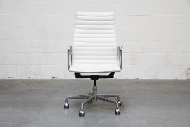 A stylish white leather 'Aluminum Group' Executive Desk chair by Charles and Ray Eames for Herman Miller. This example was part of their 50 Years commemorative label line produced only that year. Signed underneath seat with Herman Miller labels and