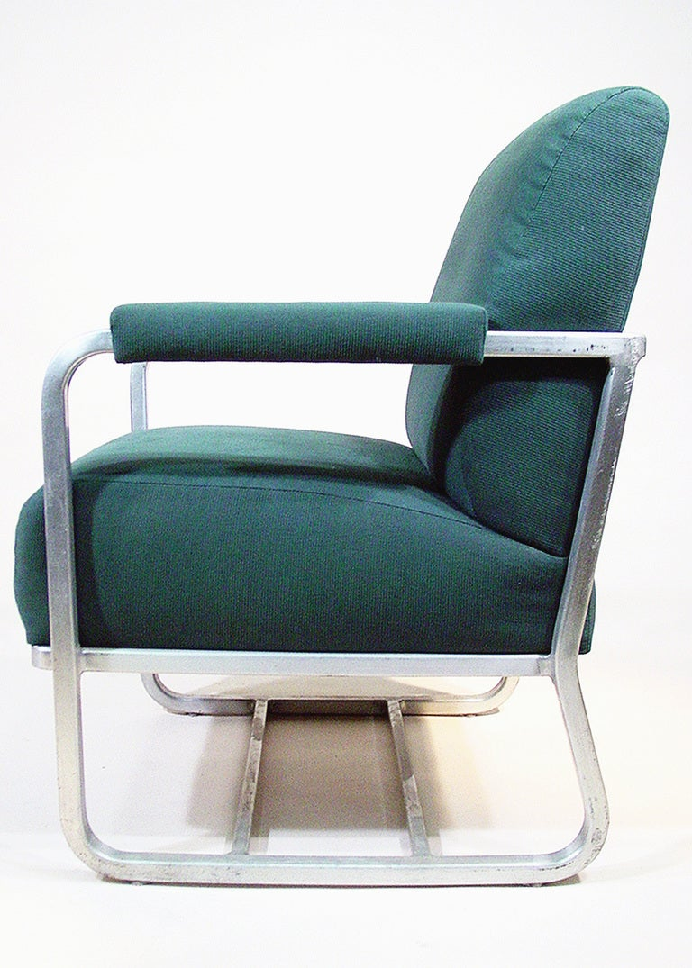 These Art Deco aluminum lounge chairs were acquired from a Pullman passenger train remodeled in the 1960s. The chairs feature tubular aluminum frames and forest green upholstery. 